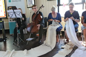 Photograph of several people, a man with a double bass,and women sewing