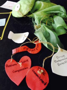A series of post-it notes, red hearts and green ribbon